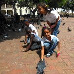 Dominican children feed the pigeons